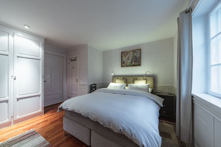 Bedroom with an private en-suite bathroom, wardrobe, dresser and a Chromecast enabled TV.