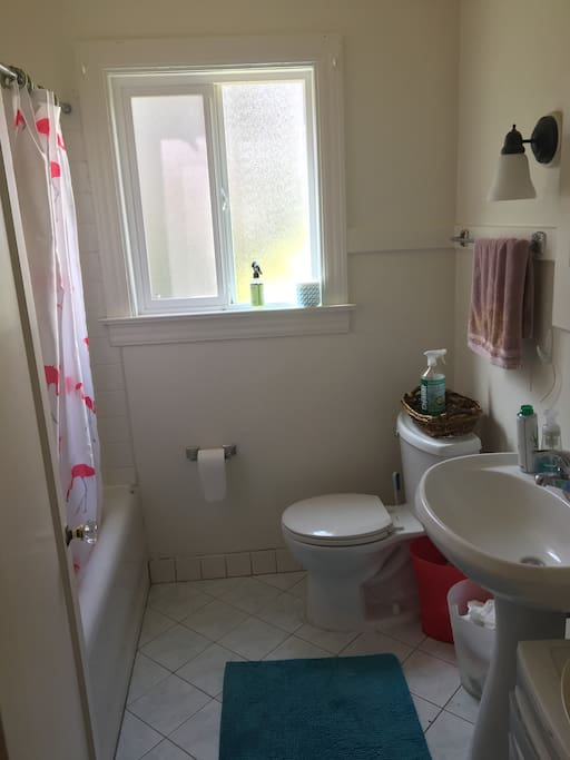 Shared bathroom with tile floors and shower/bathtub.