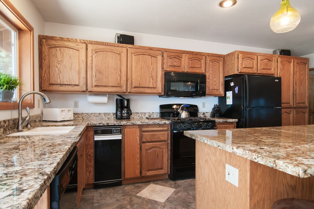 Spacious kitchen w/granite counters, new appliances, island bar seating