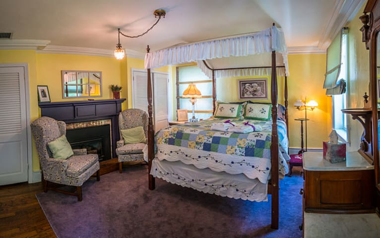 Queen bedroom with four poster canopy bed and gas fireplace.