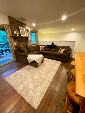 Cozy living room area couch facing smart TV.  Rustic room opens out onto deck.  Bar separates kitchen from living room.  Main bedroom is just off kitchen area.  Toddler room is located at the top of the staircase at end of the couch.