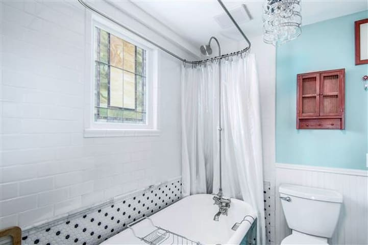 DOWNSTAIRS BATHROOM: What a fun bathroom! You have a restored antique tub/shower and corner sink with beach decor.