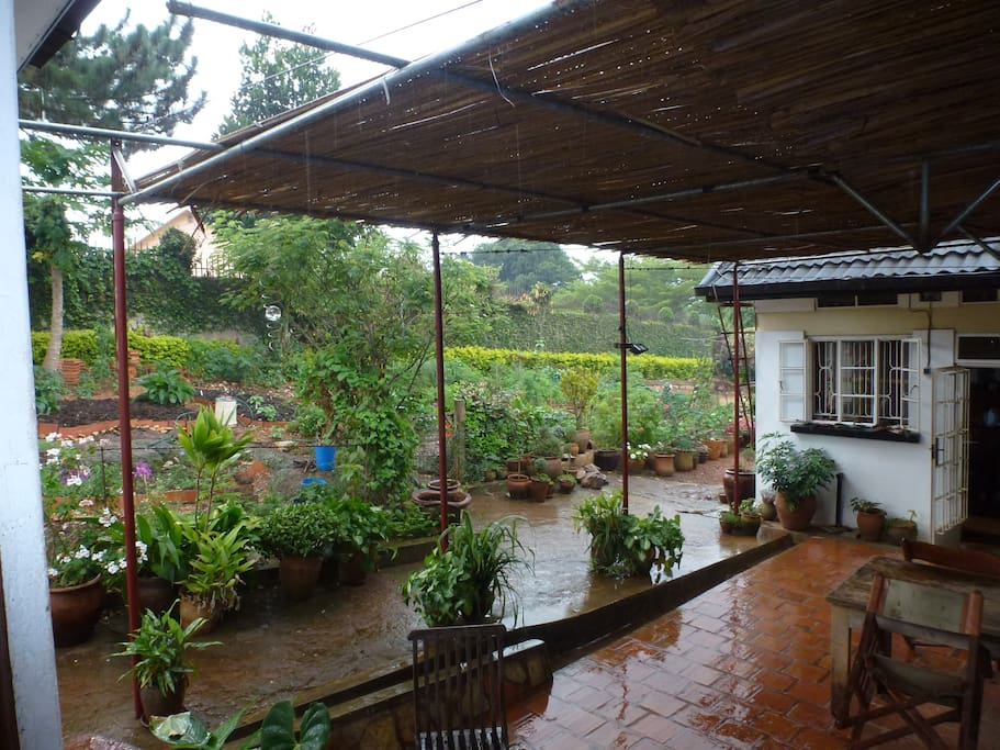 Breakfast terrace with view from guest house of organic vegetable garden and main house (kitchen)