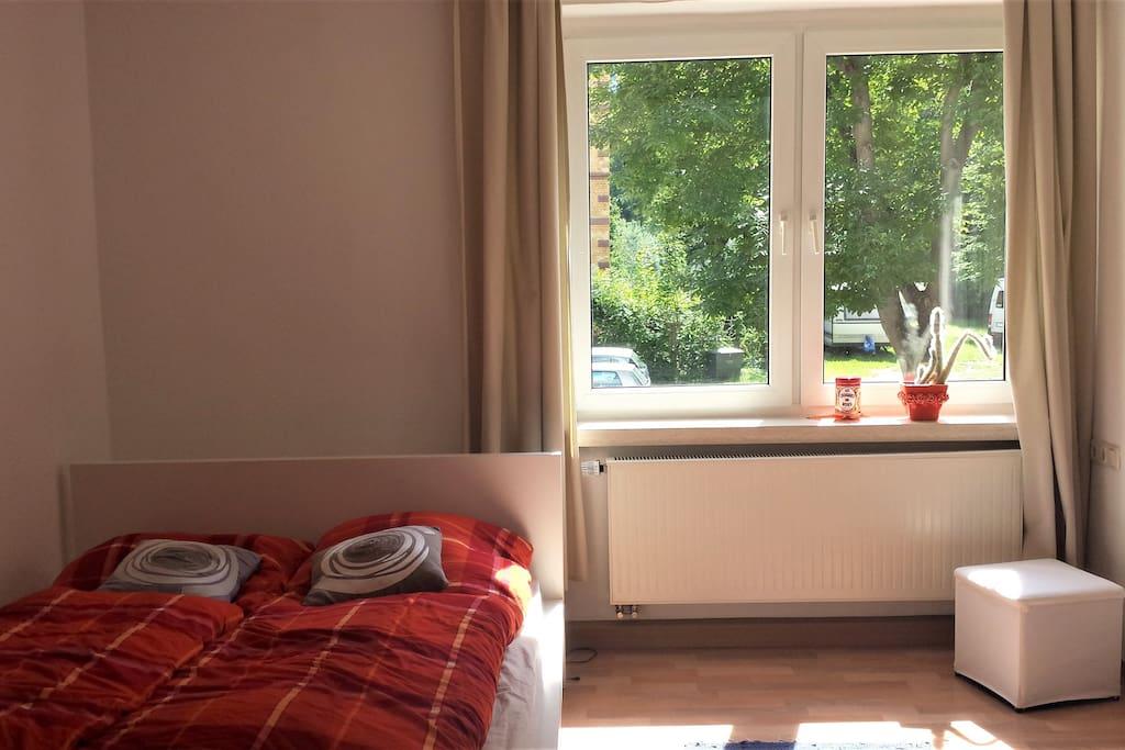 Im Schlafzimmer befinden sich ein Doppelbett, ein Kleiderschrank und eine zusätzliche Kleiderstange.