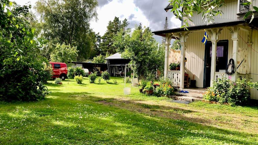 Göästrummet ligger i röda huset i bakgrunden. Du parkerar utanför dörren i den härliga trädgården.