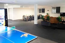 Entertaining area with a big TV, table tennis, vending machines, tables and seats