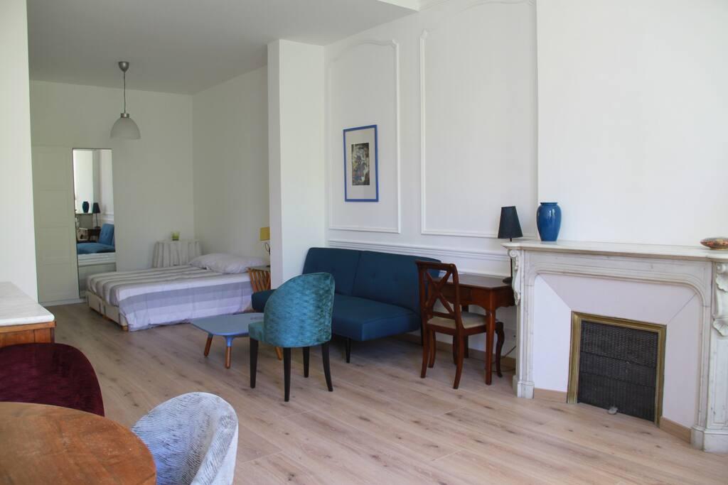 Le séjour depuis le coin repas qui mène à la cuisine. L'appartement est situé dans un ancien hôtel particulier très calme et vient d'être refait à neuf. Il donne sur les jardins.