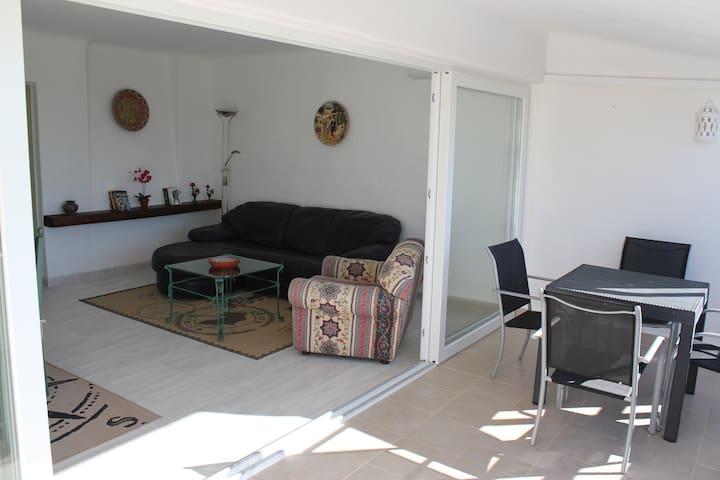 Wohnzimmer mit Essecke, Klimaanlage und großer Fensterfront
