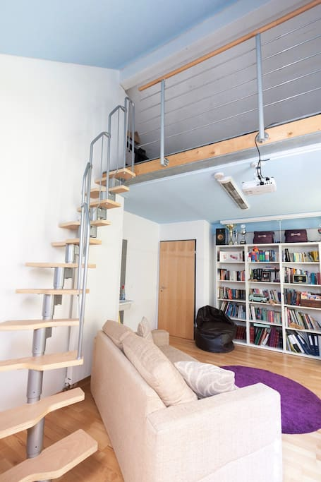 Steps to mezzanine floor, book collection, hifi system and seating.