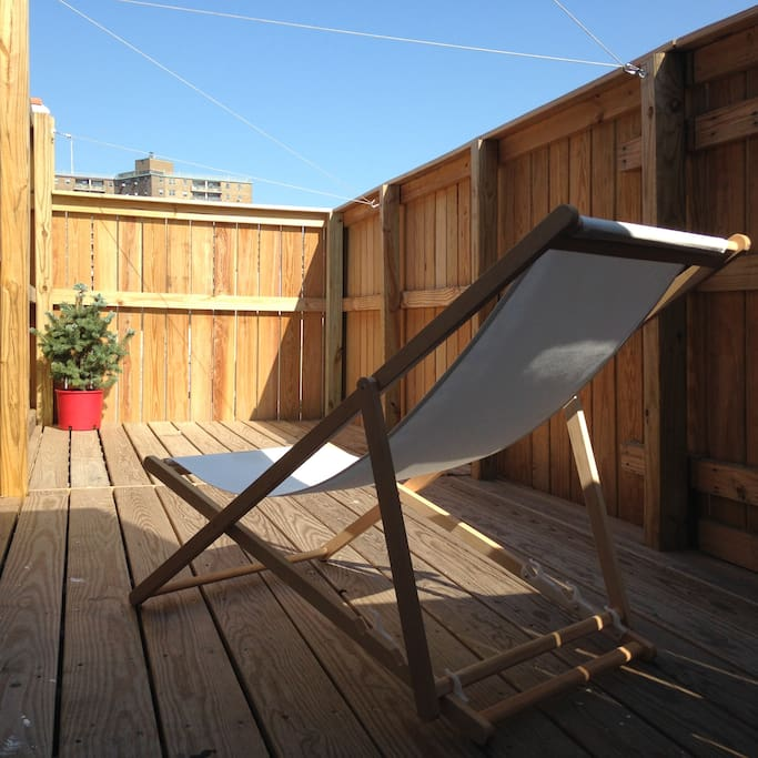 Small terrace comes with clothesline, two folding chairs and a baby christmas tree