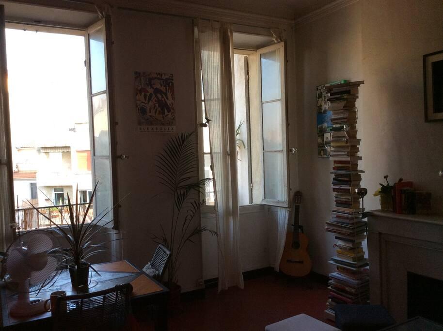 Salon avec deux grandes fenêtres ne donnant pas sur la rue mais sur des cours et jardins
