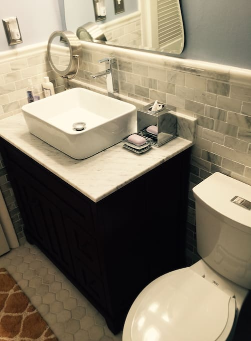 Beautiful new bathroom with marble tile on the floors and walls, new toilet, and new basin sink.  The cabinet is made from cherry wood and topped with carrera marble.