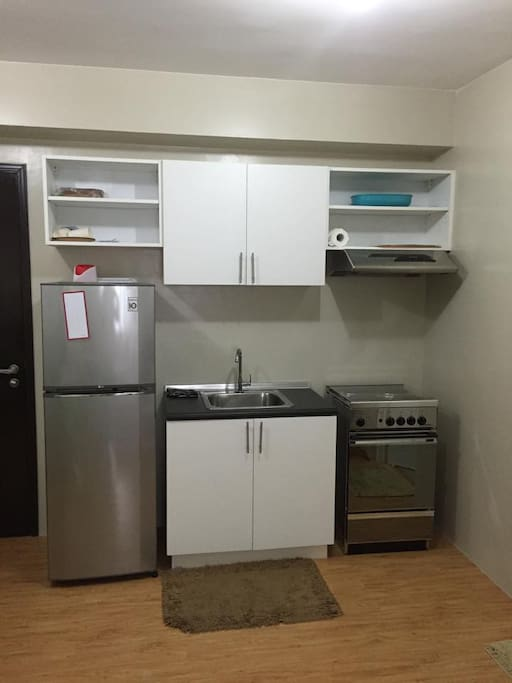 fridge, stove, microwave, electric kettle, flatware and utensils