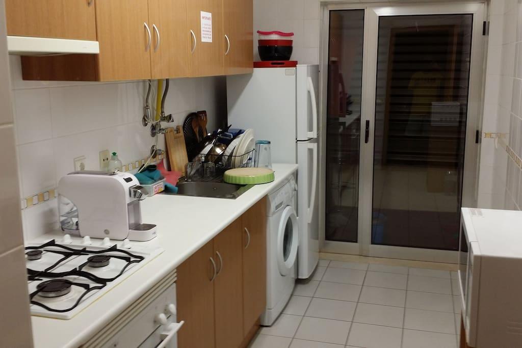 Fogão, geladeira, lavanderia, máquina de café e sacada.