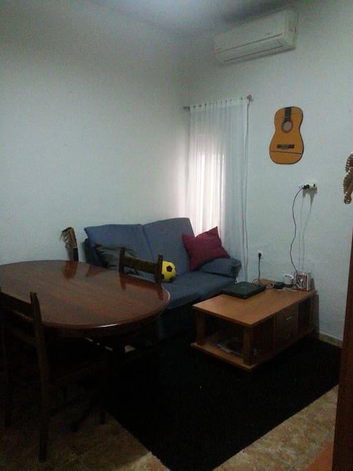 salón con aire acondicionado mesa-comedor y sofa y mesa de noche.
