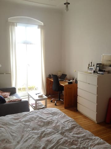 Bright airy room with large bed, balcony, and sofa - Berlin