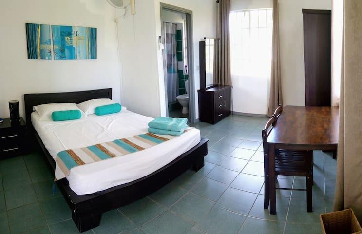 La chambre 2 en-suite, avec son armoire, son petit bureau, sa coiffeuse et la salle-de-bain attenante. Equippée de clim et ventilateur