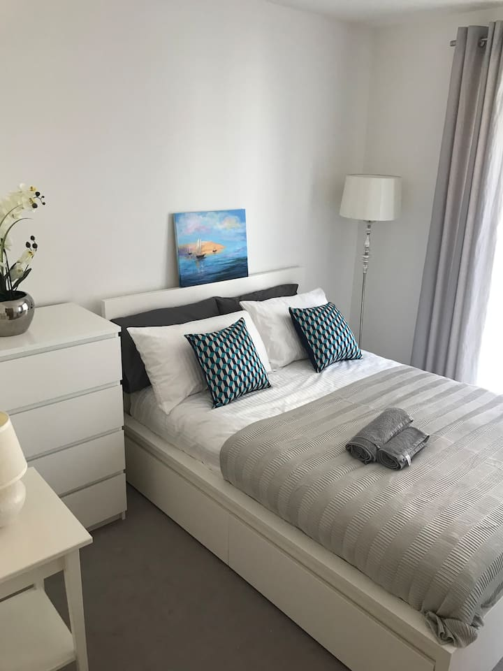 A lovely double bedroom with comfortable double bed, chest of drawers, big mirrored wardrobe and a standing lamp.