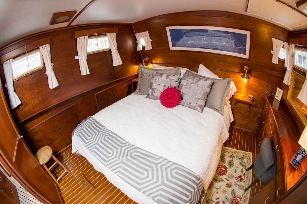 large master stateroom with queen size bed and luxury linens
