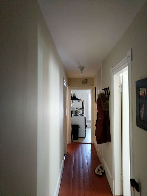 Hallway gives access to bedrooms, bathroom, kitchen and exit door