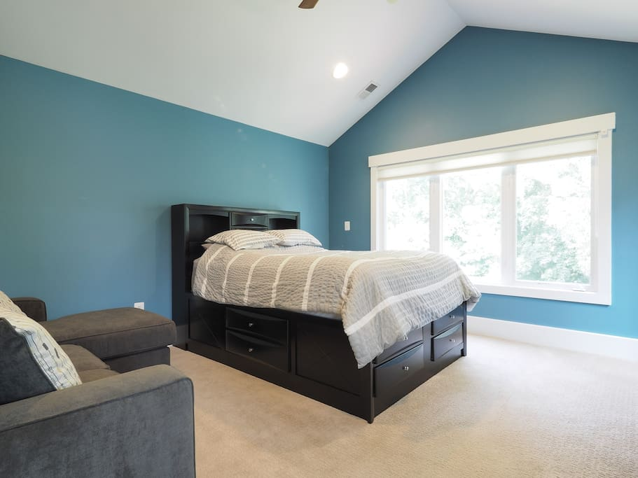 Blue Master Suite with queen size bed and small couch