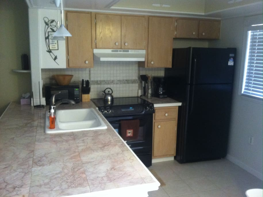 Kitchen with convection oven, dishwasher,toaster, coffee maker, tea kettle, blender, and kitchen utensils