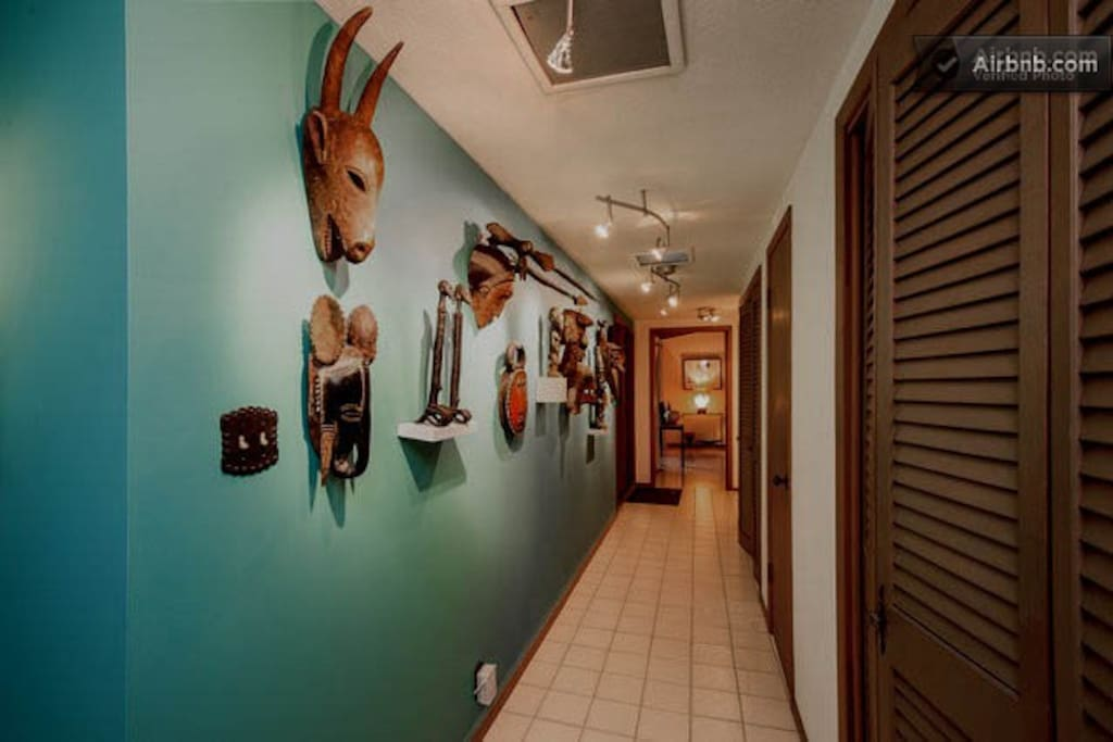 This is a shot of our entrance hall from the family room.  Cheryle and I combined our African Mask collection when we came together and they are all displayed here.    Except during Christmas, you will also see a lovely sculpture by Cathy Rose when you en