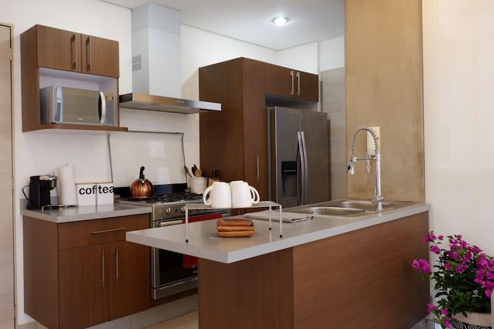 Modern kitchen with microwave, utensils, dishware, and water-dispensing fridge.