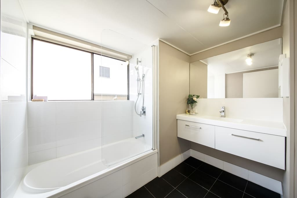 Modern, clean and airy bathroom with hidden laundry.