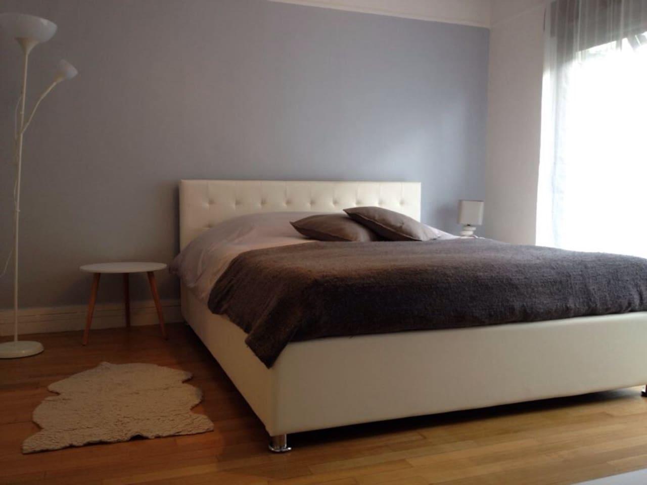 Chambre lumineuse avec vue jardin avec un grand lit 160 x 200