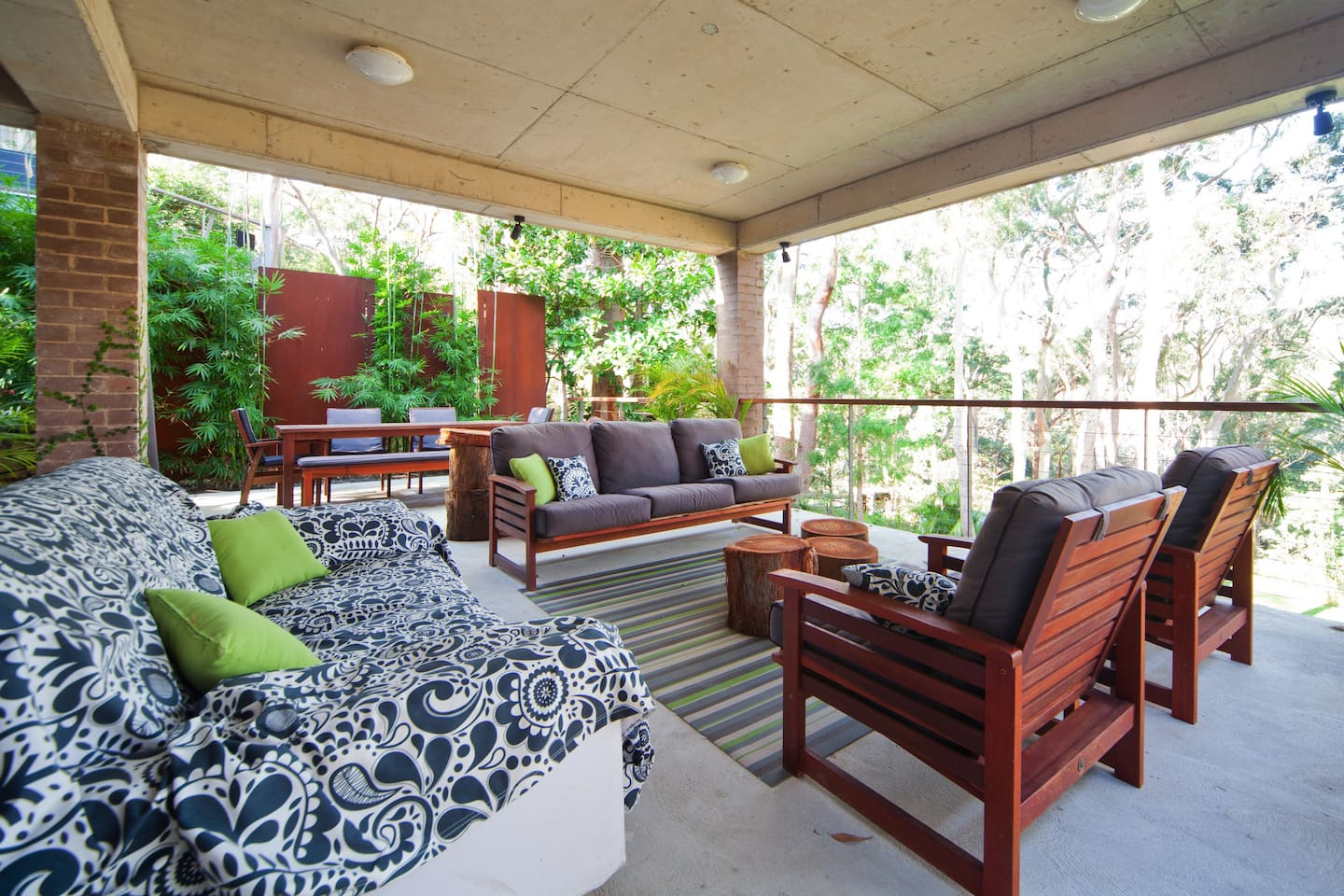 Shaded comfortable seating area on lower deck overlooking garden