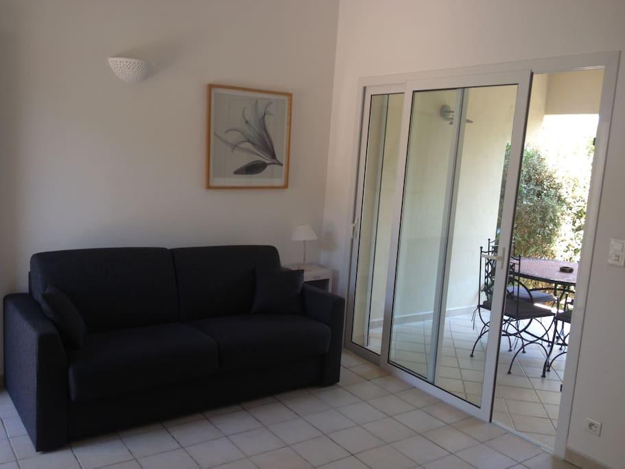 salon avec canapé lit ouverture sur terrasse couverte