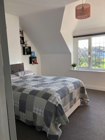 Light spacious double bed in our beautiful home.