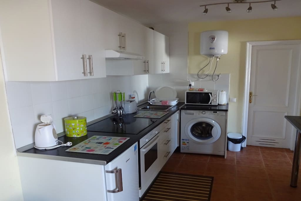 Kitchen area with oven, hotplate, fridge, microwave and washing machine