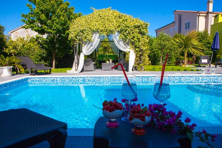 Swimming pool , arbor of white jasmine and garden with palm trees,olives and cherries ...