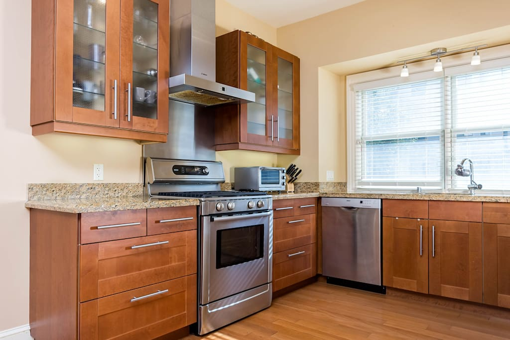 Modern, well-appointed kitchen with granite countertops, high-end appliances, and kitchenware