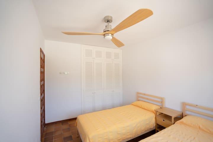 Habitación 3 con 2 camas individuales de 90cm de ancho. Ventilador de techo y armario empotrado. Vistas al patio y jardín trasero de la casa.