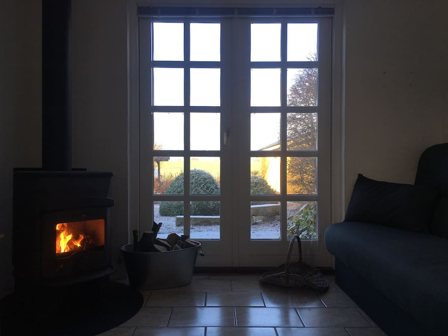 Brændeovnen og udsigten fra sovesofaen // The fireplace and the view from the sofabed