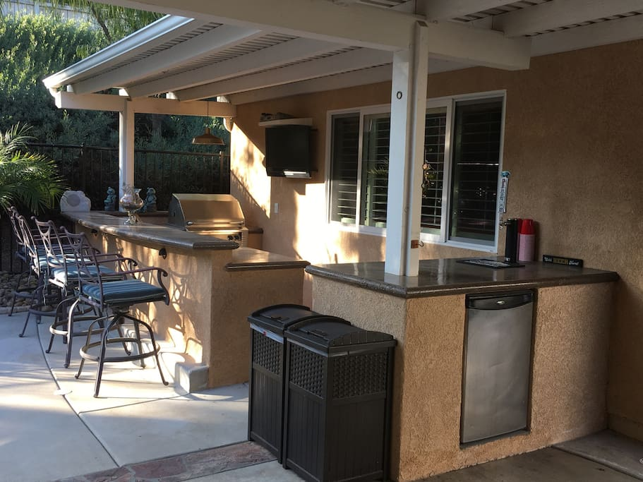 Outdoor cooking and entertainment area; BBQ, TV, Bar and refrigerator.