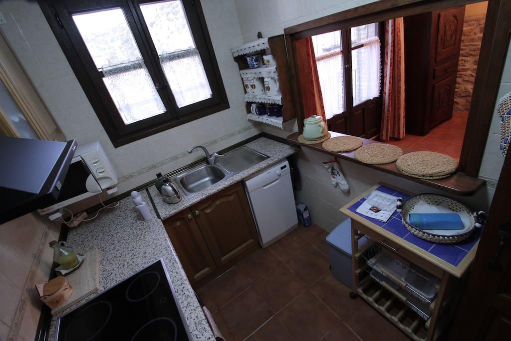 Cocina equipada con horno lavaplatos y microondas abireta al comedor