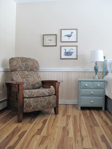 Comfy recliner and nightstand with drawers.
