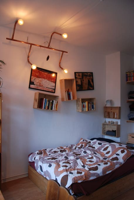 Self made dimmable LED lamp above a cosy wooden bed