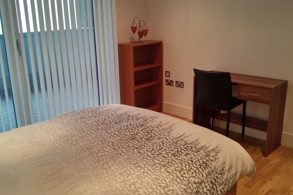 2nd view of bedroom//plenty of storage - wardrobe, chest of drawers, desk, bookcase//own door opens onto very large apartment balcony