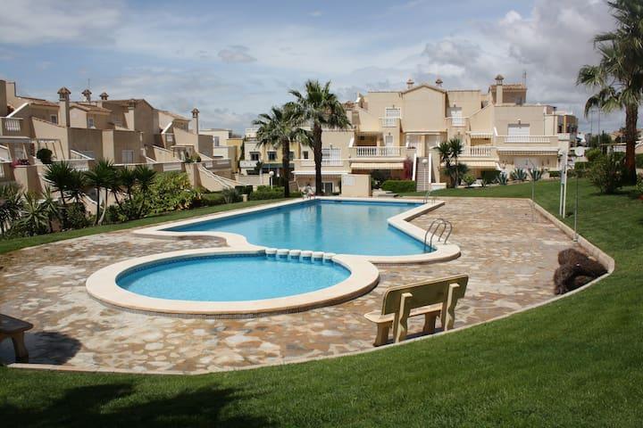Geschakelde vakantiewoning rond gedeeld  zwembad