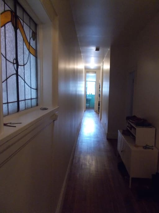 Very long hall with a stain glass window and wooden floors throughout.