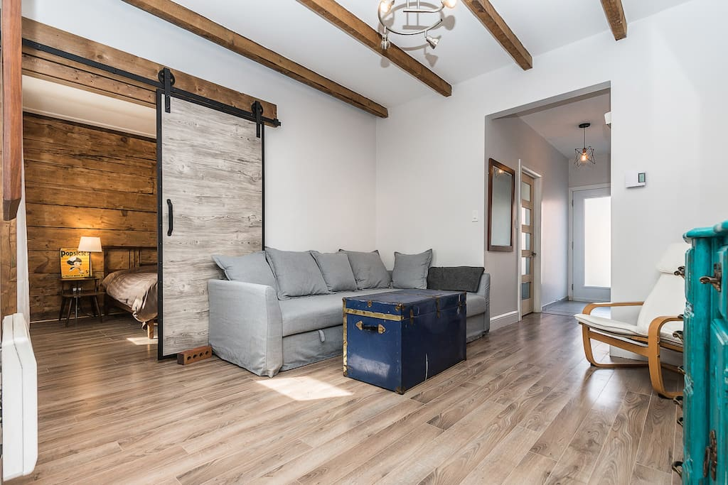 Exposed wood beams and sliding barn door leading to second bedroom