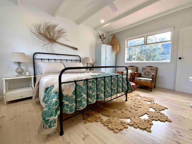 Second bedroom with queen size bed. Beautiful french linen and quality bedding set in a rather spacious room. You will find spare blankets and board games within the cupboards and twin chairs to sit back and relax away from the main living area.
