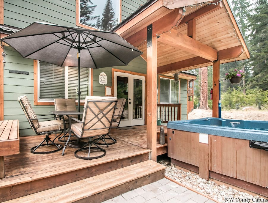 Back deck with outdoor seating, hot tub and backed by the trees.