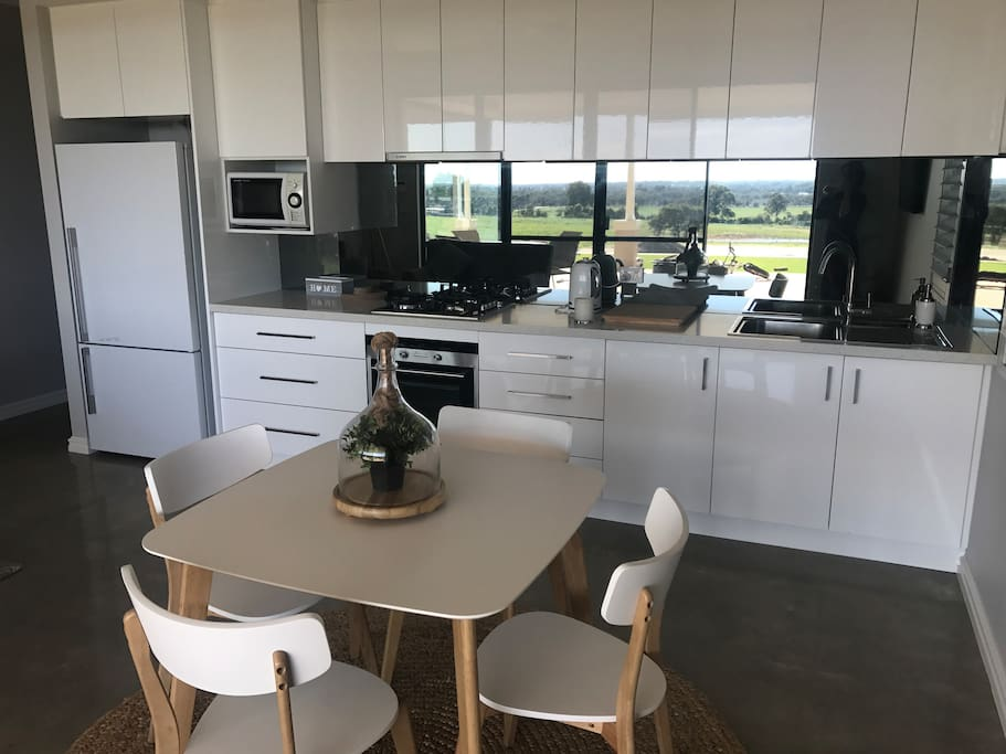 Kitchen , dining area , just look at the view through the splashback ! Fridge /freezer , microwave , oven and gas cooktop . Kettle and toaster , tea & coffee included . Triple filtered rain water for drinking