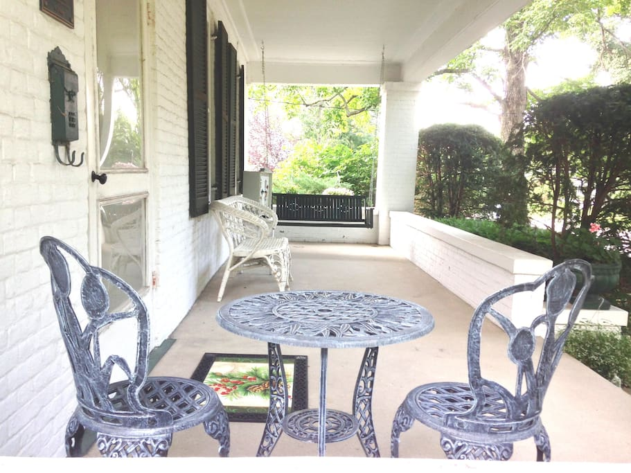Very quaint front porch with swing, wicker furniture and tea table.